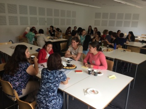 Postgraduate student parents talk to each other around tables